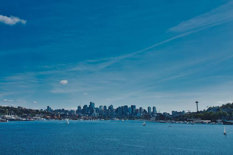 The cityscape of Seattle in the background of Lake Union. Sailboats are out, and the space needle can be seen.
