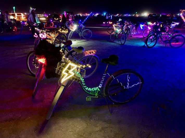 bicycles lit up at night in black rock city desert of burning man