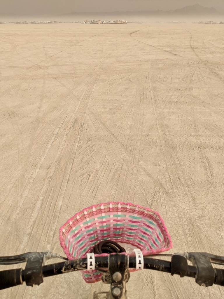 Riding a bicycle into the expansive desert with camps far in the distance