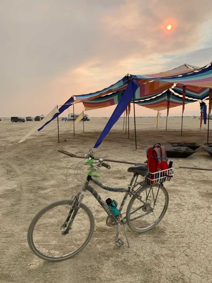 A single bicycle in front of the burning man temple shade structure