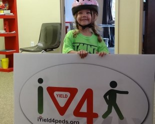 BWCF fits its newest bicyclist, Nevaeh, with a bike helmet