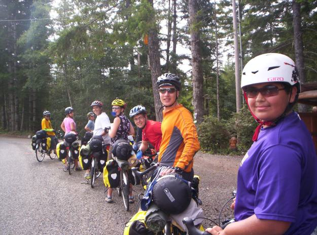 A group of youth pose with their bikes and camping gear in the forest