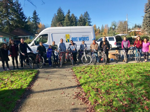 A group of adults stand with their bikes in front of a white van with the Bike Works logo on it