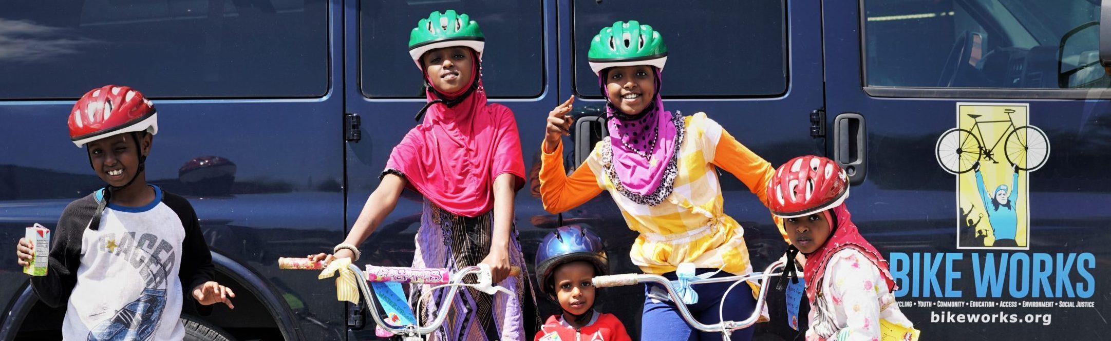 Five kids in bicycle helmets posing with bicycles in front of a navy blue Bike Works van.