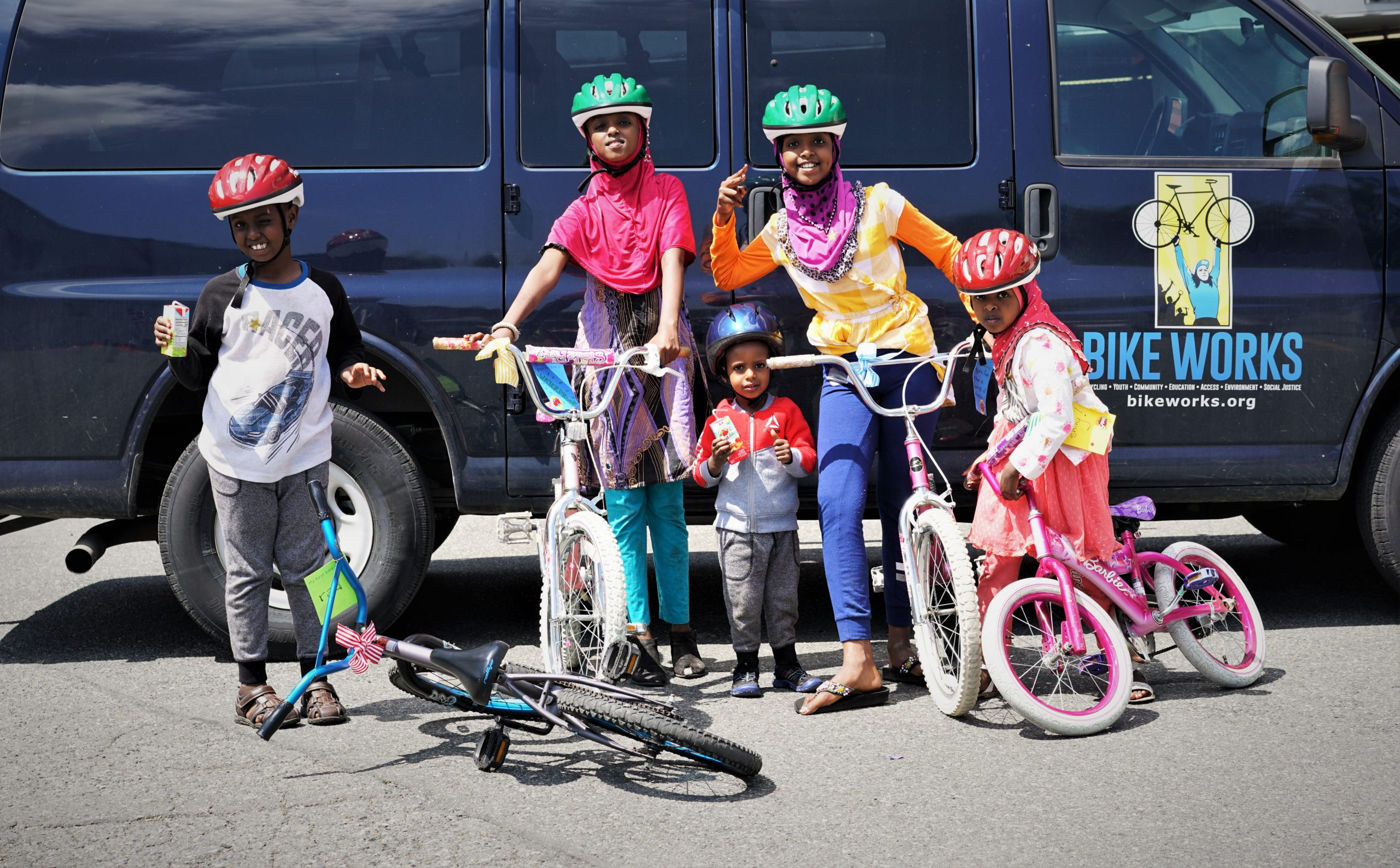 Five kids in bicycle helmets posing with bicycles in front of a navy blue Bike Works van.