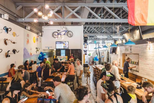 A crowded brewery with a bike on the far wall and a rainbow flag on the right.