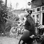 A profile of a cyclist with a mask and helmet on in Black & White