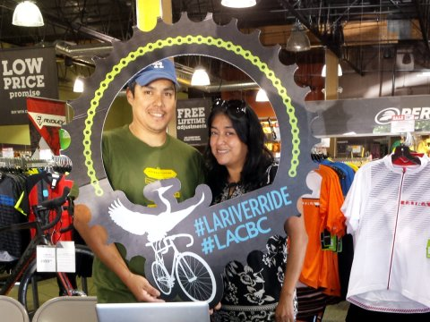 Adrian Oviedo and Sandy Brambila pose with the LACBC River Ride logo at Performance Bike in Long Beach