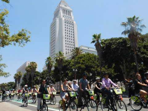 Riders roll out with LA City Hall as a backdrop