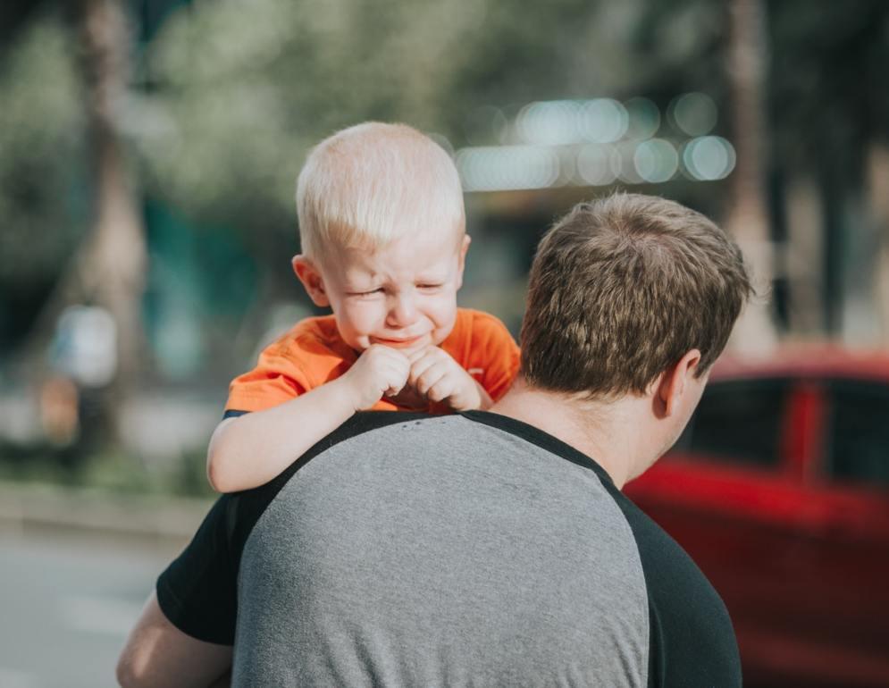 Tata niosący płaczące dziecko