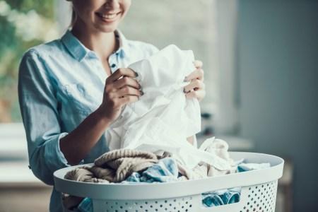 Młoda kobieta trzymająca w dłoniach pranie.