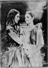 Eine junge Frau mit langen Haaren legt einer jungen Frau mit kurzen Haaren eine Stola um. Schwarz-Weiß