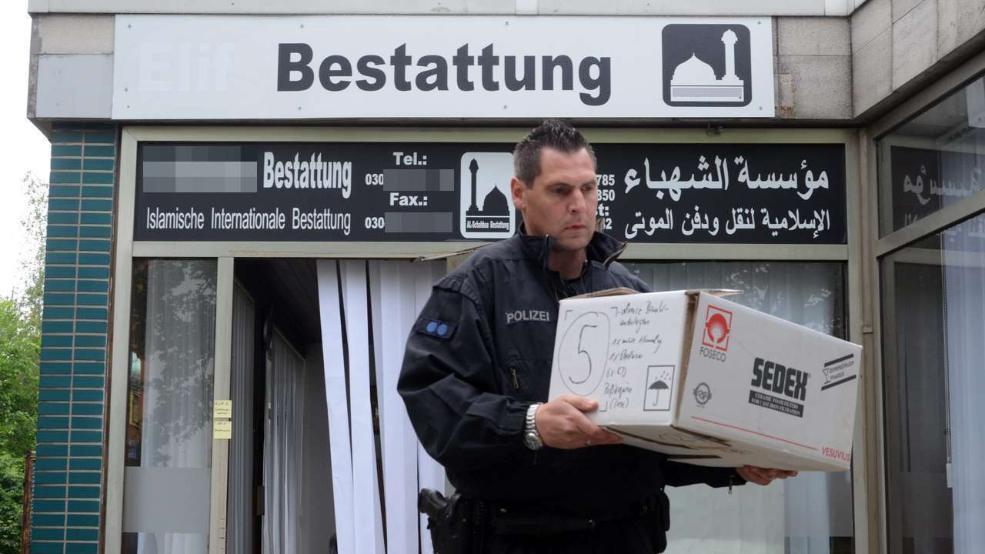 Der Polizist trägt einen Karton mit Beweismitteln aus dem Bestattungsinstitut
