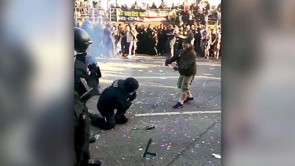 Ein Chaot wirft einem Polizisten einen Böller direkt ins Gesicht