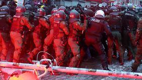 """Polizeibeamte drängen vor dem Kulturzentrum """"Rote Flora"""" die Demonstranten zurück."""