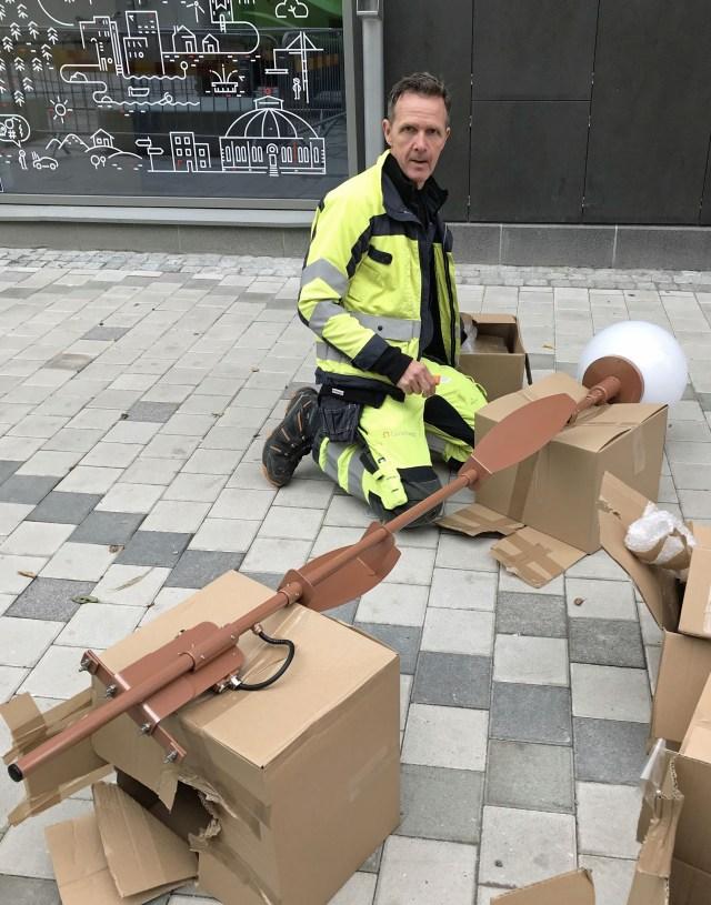 Anders Enroth från Gävle energi monterar en av de lampor som ska sprida ljus över Drottninggatan.