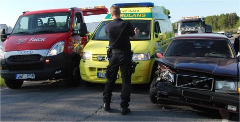 Polisen lotsar fram en förbipasserande ambulans mellan en bärgningsbil och den krockade Volvon