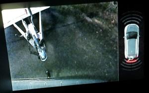 Bild i mittkonsolens bildskärm från backkameran och med varningssignal från parkeringshjälpens ultraljudsensorer