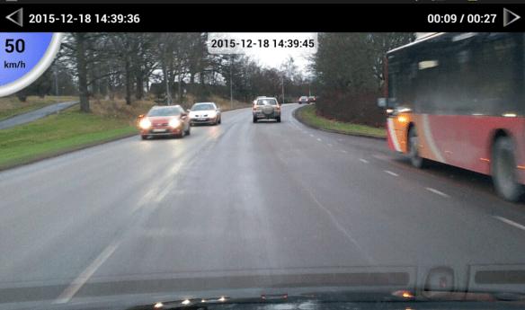 Skärmdump från videofilmad körning intill buss på 50-sträcka med lastbil nära bakom.