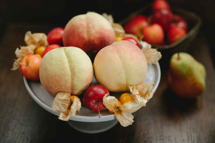delicious peaches apples and cape gooseberries on table