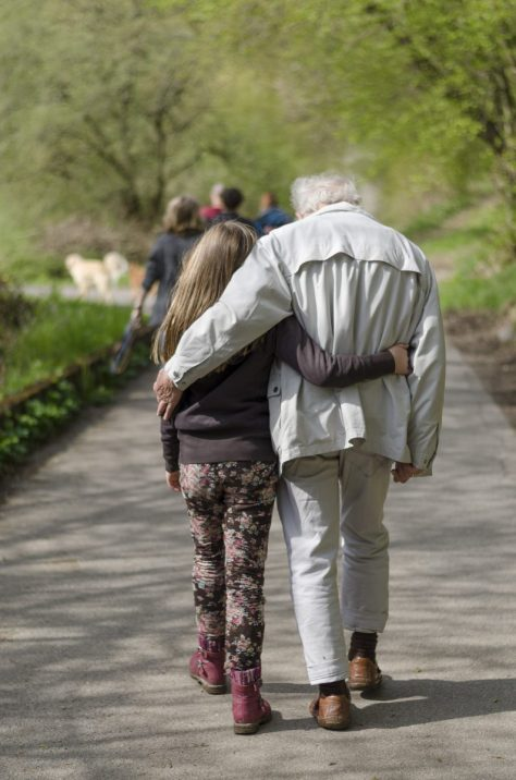 Young girl walking with an old man.