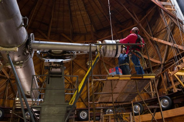 Workers prepare to lift a counterweight through the open shutter of the Clark Dome at Lowell Observatory.