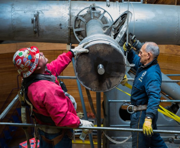 Lowell Observatory's Ralph Nye (on right in blue jacket) inspects progress toward removing one of the 400-lb. counterweights from the mount of the Clark Refractor.