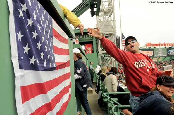 """""""Fans greet each other in the Green Monster Seats during the first Boston Red Sox home game after the attacks on the 2013 Boston Marathon Saturday, April 20, 2013."""""""