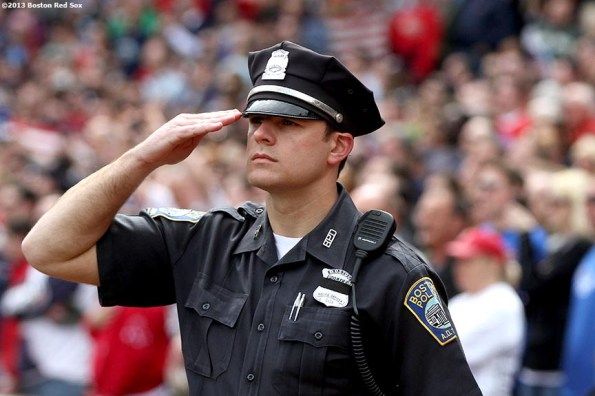 """""""A Boston Police Officer salutes the flag during a pre-game ceremony honoring the victims, first responders, and others involved in the attacks on the 2013 Boston Marathon Saturday, April 20, 2013."""""""