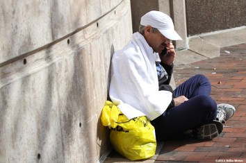 April 15, 2013 - Boston, Massachusetts, United States: A Boston Marathon runner makes a phone call near Copley Square after two bombs were detonated at the finish line of the 2013 Boston Marathon. (Billie Weiss)