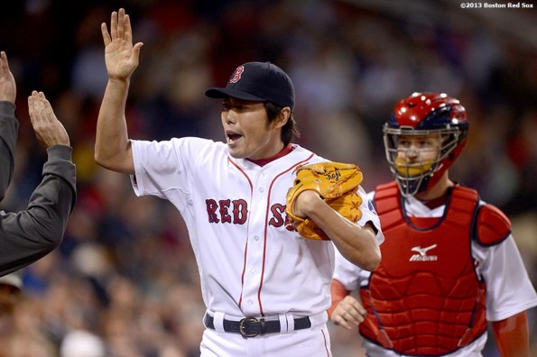 """""""Boston Red Sox reliever Koji Uehara high fives teammates after retiring the side in order during the eighth inning of a game against the Minnesota Twins Thursday, May 9, 2013 at Fenway Park."""""""