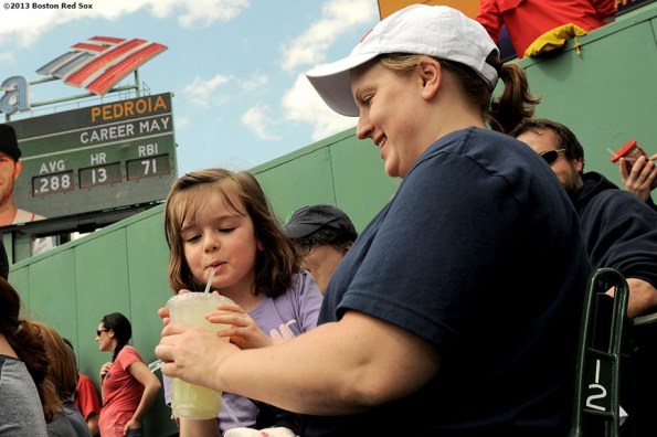 """""""A young fan in the bleacher seats drinks lemonade as her mother watches during a game between the Boston Red Sox and the Toronto Blue Jays on Mother's Day at Fenway Park Sunday, May 12, 2013 in Boston, Massachusetts."""""""