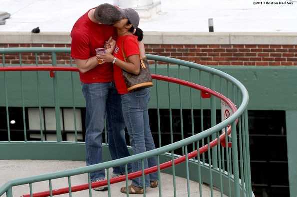 """""""A couple kisses each other on the stairs inside Gate B during a game between the Boston Red Sox and the Toronto Blue Jays on Mother's Day Sunday, May 12, 2013 at Fenway Park in Boston, Massachusetts."""""""
