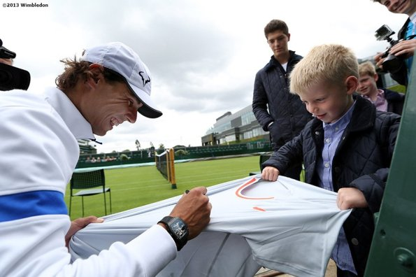 """""""Rafael Nadal signs an autograph after a practice session at the All England Lawn and Tennis Club in London, England Saturday, June 22, 2013 before the start of the 2013 Championships Wimbledon."""""""