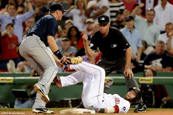 """""""Boston Red Sox second baseman Dustin Pedroia dives back to first base after getting caught in a rundown during the fourth inning of a game against the Seattle Mariners Tuesday, July 30, 2013 at Fenway Park in Boston, Massachusetts."""""""