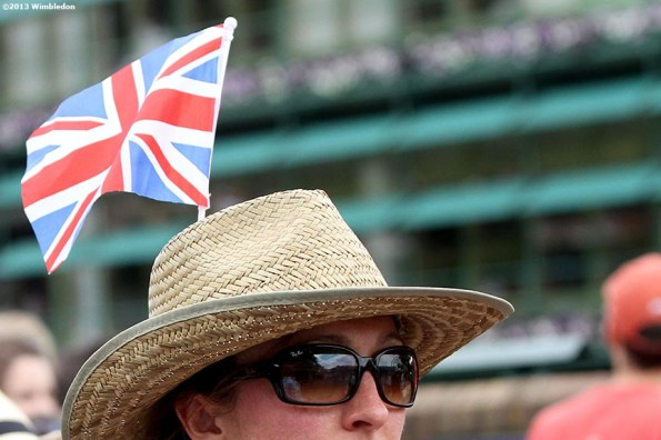 """""""A fan walks with a British flag attached to her hat at the All England Lawn and Tennis Club in London, England Monday, July 1, 2013 during the 2013 Championships Wimbledon."""""""