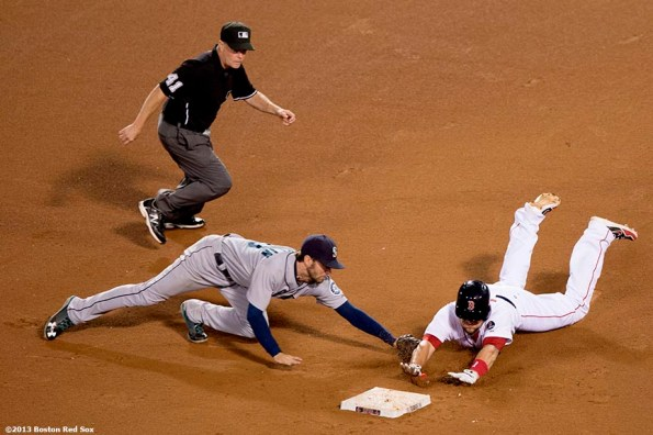 """""""Boston Red Sox third baseman Brandon Snyder slides into second base and evades a tag by second baseman Nick Franklin during the fourteenth inning of a game against the Seattle Mariners Wednesday, July 31, 2013 at Fenway Park in Boston, Massachusetts."""""""