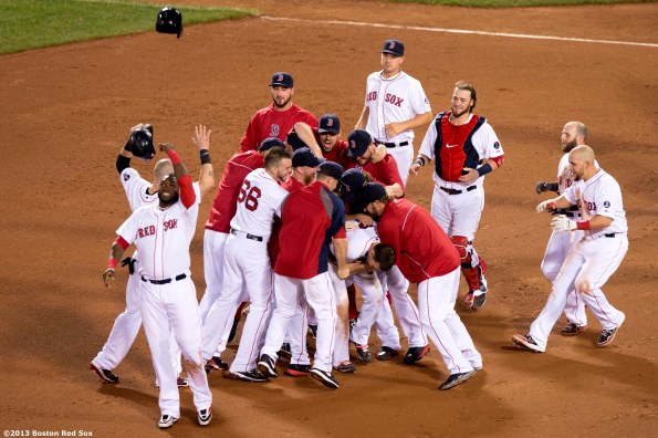"""""""Boston Red Sox teammates mob shortstop Stephen Drew after Drew hits a game winning RBI single with the bases loaded during the bottom of the fifteenth inning of a game against the Seattle Mariners Thursday, August 1, 2013 at Fenway Park in Boston, Massachusetts."""""""