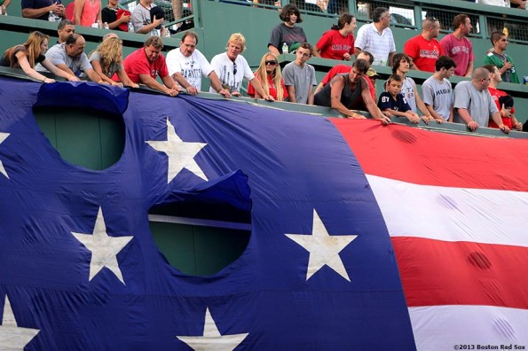 """""""Fans help drop the American flag over the Green Monster during a Military appreciation ceremony before a game between the Boston Red Sox and the Seattle Mariners Wednesday, July 31, 2013 at Fenway Park in Boston, Massachusetts."""""""