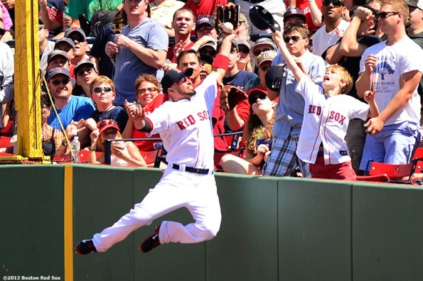 """""""Boston Red Sox right fielder Shane Victorino leaps the wall as he attempts to make a catch during the third inning of a game against the Arizona Diamondbacks Sunday, August 4, 2013 at Fenway Park in Boston, Massachusetts."""""""