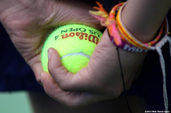 """""""A ball girl holds a tennis ball behind her back on Day 2 of the New Haven Open at Yale University in New Haven, Connecticut Saturday, August 17, 2013."""""""