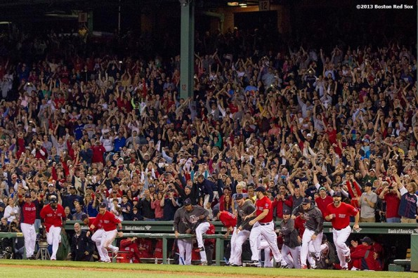 """""""Boston Red Sox teammates run out of the dugout in celebration after recording the final out of a 6-3 win over the Toronto Blue Jays to clinch the American League East title at Fenway Park Friday, September 23, 2013."""""""