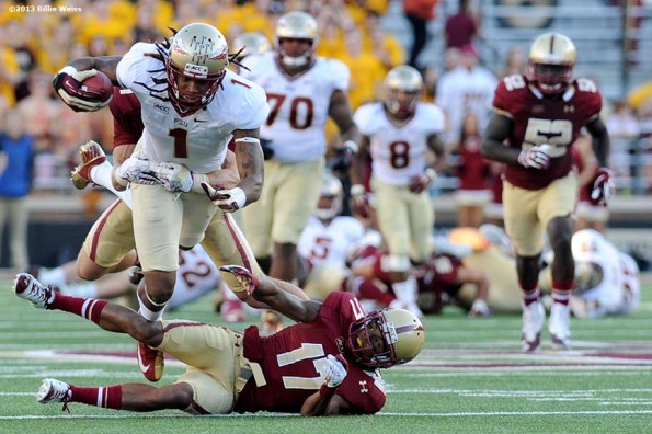 """""""Florida State Seminoles wide receiver Kelvin Benjamin leaps over defensive back Bryce Jones during the third quarter of a game against the Boston College Eagles at Alumni Stadium in Chestnut Hill, Massachusetts Saturday, September 28, 2013."""""""