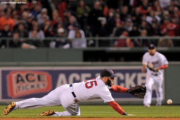 """""""Boston Red Sox second baseman Dustin Pedroia makes a diving stop on a ground ball during the third inning of game two of the American League Championship Series against the Detroit Tigers Sunday, October 13, 2013 at Fenway Park in Boston, Massachusetts."""""""