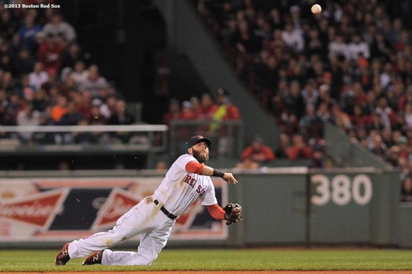"""""""Boston Red Sox second baseman Dustin Pedroia throws to first base after making a diving stop on a ground ball during the third inning of game two of the American League Championship Series against the Detroit Tigers Sunday, October 13, 2013 at Fenway Park in Boston, Massachusetts."""""""