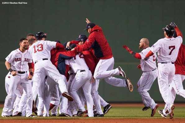 """""""Boston Red Sox players mob catcher Jarrod Saltalamacchia after Saltalamacchia hit a game-winning RBI single during the ninth inning of game two of the American League Championship Series against the Detroit Tigers Sunday, October 13, 2013 at Fenway Park in Boston, Massachusetts. The Red Sox came back from a 5-0 deficit to defeat the Tigers 6-5."""""""