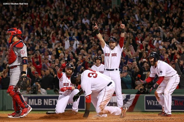 """""""Boston Red Sox designated hitter David Ortiz slides into home plate as right fielder Jonny Gomes, center fielder Jacoby Ellsbury, and second baseman Dustin Pedroia celebrate after scoring on a double by first baseman Mike Napoli during the first inning of game one of the 2013 World Series against the St. Louis Cardinals Wednesday, October 23, 2013 at Fenway Park in Boston, Massachusetts."""""""