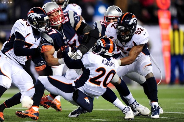 """""""New England Patriots tight end Rob Gronkowski is tackled as he drives toward the end zone during a game against the Denver Broncos Sunday, November 24, 2013 at Gillette Stadium in Foxborough, Massachusetts."""""""