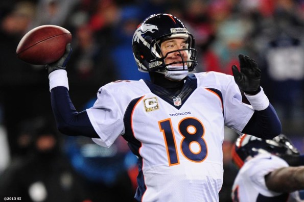"""""""Denver Broncos quarterback Peyton Manning throws a pass during a game against the New England Patriots Sunday, November 24, 2013 at Gillette Stadium in Foxborough, Massachusetts."""""""