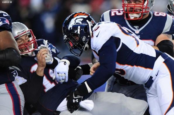 """Denver Broncos defensive end Derek Wolfe forces a fumble as he tackles New England Patriots quarterback Tom Brady Sunday, November 24, 2013 at Gillette Stadium in Foxborough, Massachusetts."""